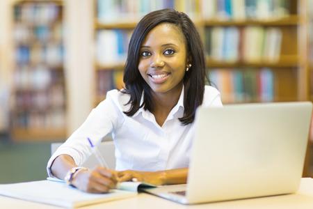 krásná afro americký student sedí v knihovně vysoké školy Reklamní fotografie