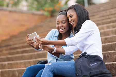 african american woman smiling: beautiful african american college students using cell phone on campus