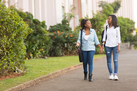 college: pretty african college students walking together on campus