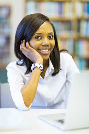 beautiful young female african college student sitting in library photo