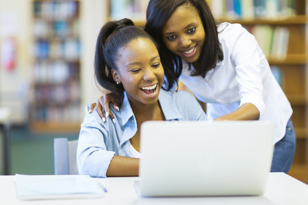cheerful african american college girls using laptop computer photo