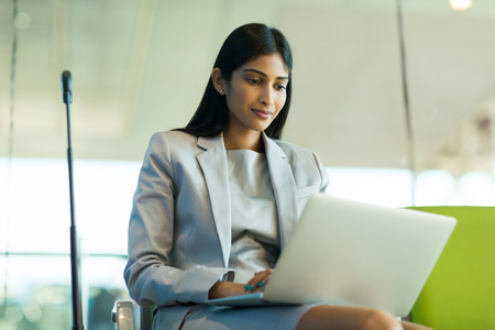 attractive indian business traveler using laptop at airport Stock Photo
