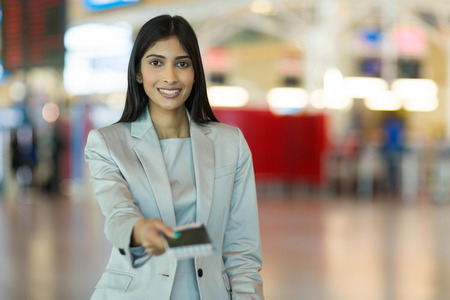 over the counter: happy indian woman handing over air ticket at airline check in counter