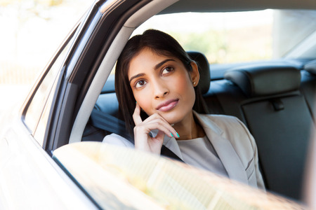 confident woman: beautiful young indian businesswoman in a taxi