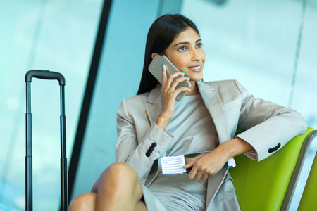 business traveller: attractive smiling business traveller talking on mobile phone at airport Stock Photo