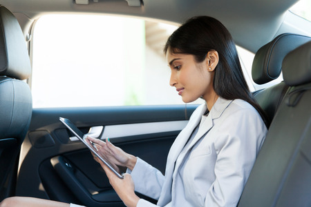 차의 뒷좌석에서 태블릿 PC를 사용하여 인도 비즈니스 여성 스톡 콘텐츠