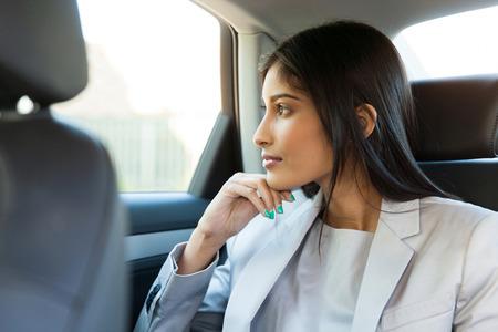 mujer reflexionando: pensativo mujer de negocios indio sentado en el asiento trasero del coche Foto de archivo