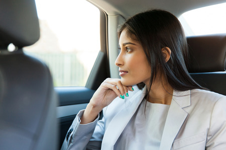 gorgeous woman: thoughtful indian business woman sitting in car backseat