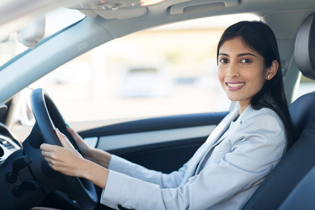 mujeres sentadas: alegre joven empresaria india conducir un coche Foto de archivo