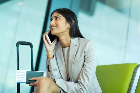 attraktive junge indische Unternehmerin spricht über Handy am Flughafen