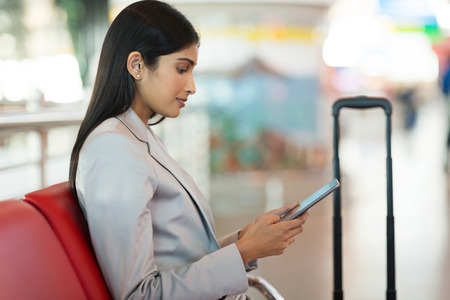 using tablet: indian businesswoman using tablet computer while waiting for her flight at airport