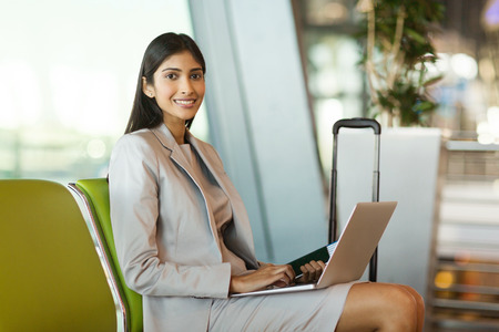 luggage travel: portrait of happy young indian woman waiting at airport lounge