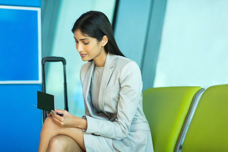air ticket: attractive indian business woman looking at her air ticket at airport Stock Photo