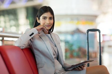 portrait of beautiful young indian woman holding tablet computer at airport