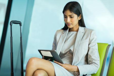 mujer elegante: hermosa joven empresaria en el aeropuerto de la lectura de sus mensajes de correo electr�nico en la computadora de la tableta