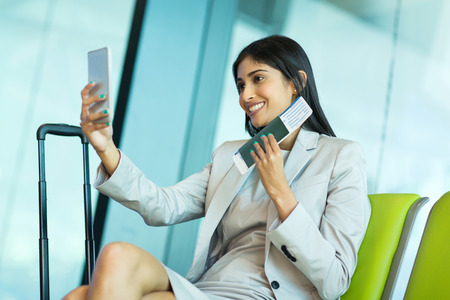 business traveller: happy young business traveller taking selfie with smart phone while waiting for her flight at airport