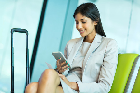 airport business: attractive young indian businesswoman using smart phone at airport