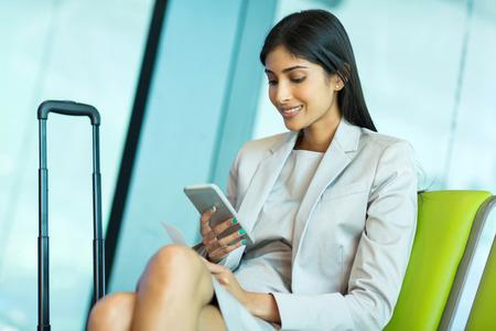 attraktive junge indische Unternehmerin Smartphone am Flughafen mit
