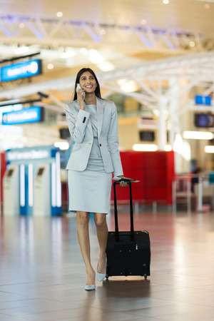 corporate airplane: attractive young businesswoman talking on smart phone at airport