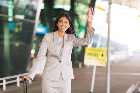 happy indian businesswoman hailing for a taxi after arriving at airport