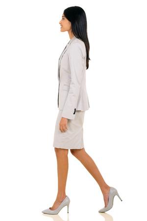 zijaanzicht van jonge Indische zakenvrouw lopen op een witte achtergrond Stockfoto
