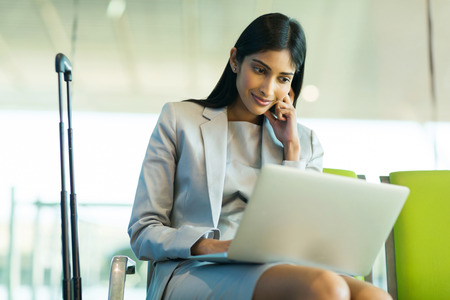 corporate travel: successful indian businesswoman using laptop computer at airport Stock Photo