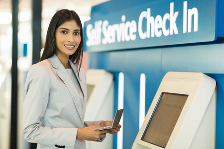 check in: gorgeous indian businesswoman using self help check in machine at airport
