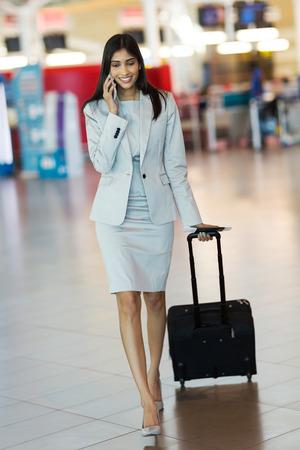 mujer elegante: exitosa mujer de negocios indio hablando por teléfono móvil en el aeropuerto internacional
