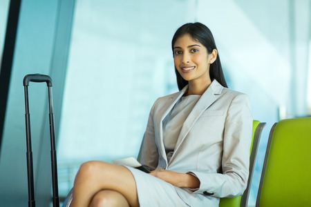 beautiful indian businessman sitting at airport waiting for her flight