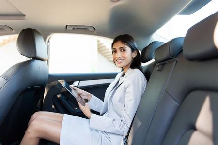 medios de transporte: bella mujer de negocios con tablet PC en un coche Foto de archivo