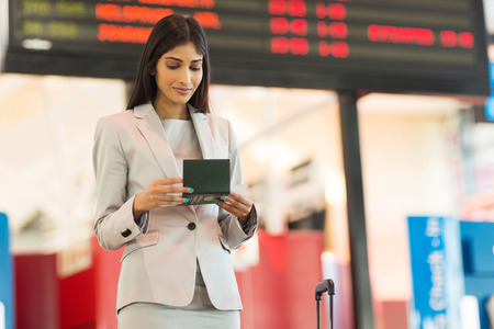 air ticket: gorgeous young indian businesswoman looking at air ticket in airport
