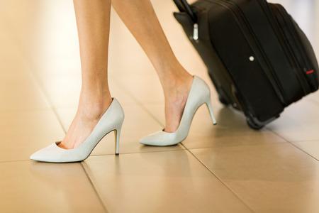 mujer con maleta: Empresaria con equipaje caminando en el aeropuerto de cerca