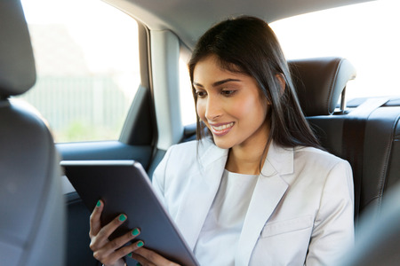 cab: happy indian businesswoman using tablet computer inside a car