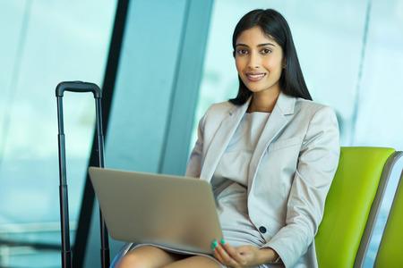 mujer elegante: feliz joven empresaria india con la computadora port�til en el aeropuerto Foto de archivo