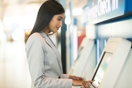 junge Geschäftsreisender mit automatisierten Check-in-Automaten am Flughafen Standard-Bild