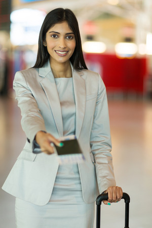 air ticket: beautiful young indian businesswoman presenting air ticket and passport at airport