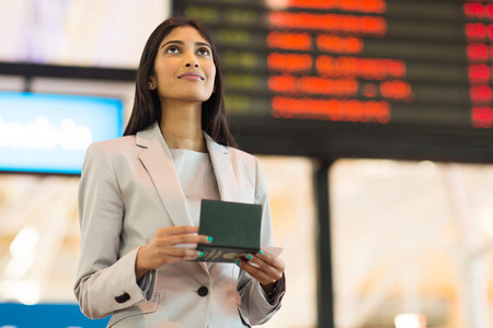 departure board: pretty indian business woman checking flight information at airport Stock Photo
