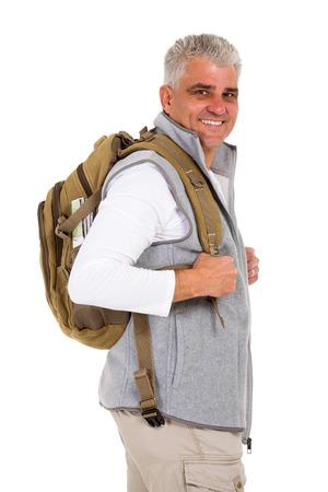 MOCHILA: Turista feliz de mediana edad mirando hacia atrás aislados en blanco Foto de archivo