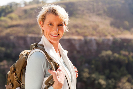mid age: happy mid age woman with backpack standing on top of the mountain Stock Photo