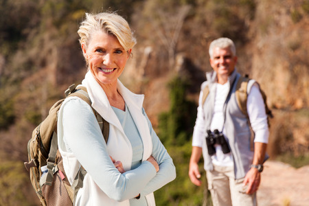 middle age: senior female hiker standing on mountain with husband on background