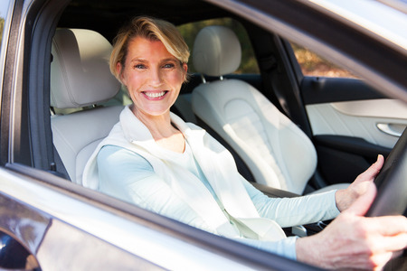 senior female: happy middle aged woman driving a car