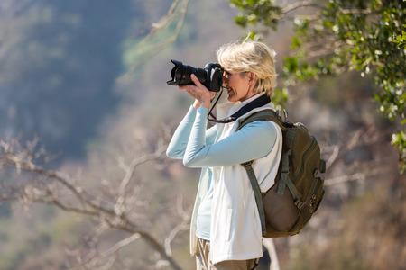 happy senior hiker taking photos with digital camera Stockfoto