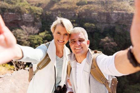 tercera edad: feliz pareja caminatas tomar selfie juntos en la cima de la montaña