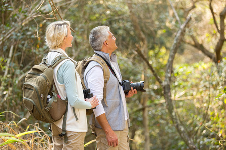 cheerful middle aged couple bird watching in forest