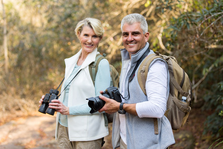 active seniors: active mature couple in forest looking at the camera