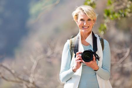 senior woman: happy senior hiker standing on top of the mountain Stock Photo