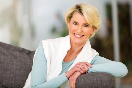 femmes souriantes: portrait de femme d'âge assez moyenne assis sur un canapé