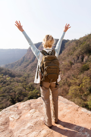 top mountain: back view of female hiker arms open on mountain cliff