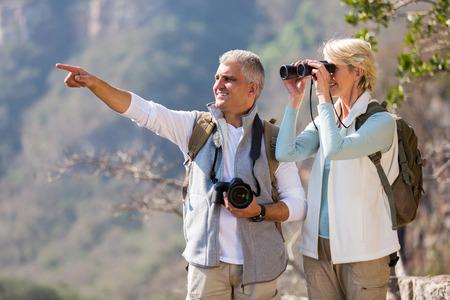 아름 다운 여성 등산객 남편을 가리키는 동안 쌍안경을 사용 하여