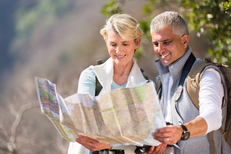people and nature: happy senior hikers looking at map